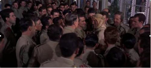 Le militaire qui sourit devant le lieutenant lui tend un verre pour le féliciter. Les autres suivent son exemple.